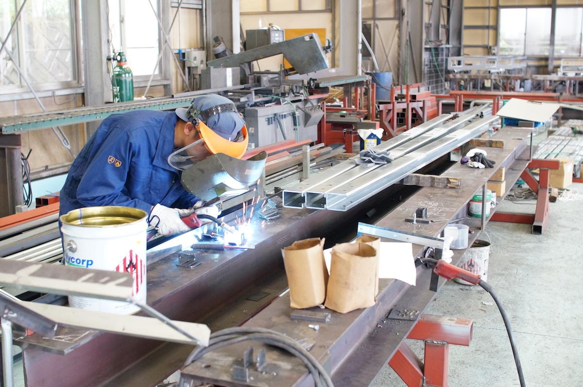 鉄工工場で溶接作業する社員